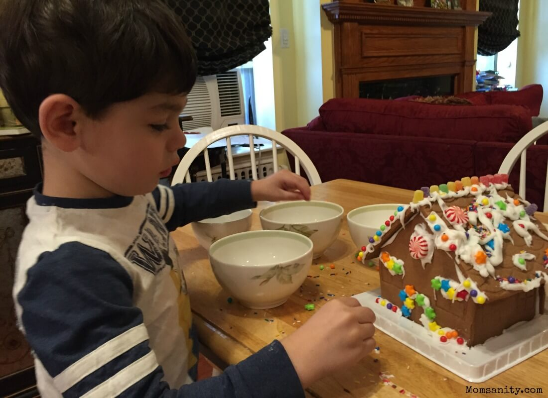 Little boy making a gingerbread house