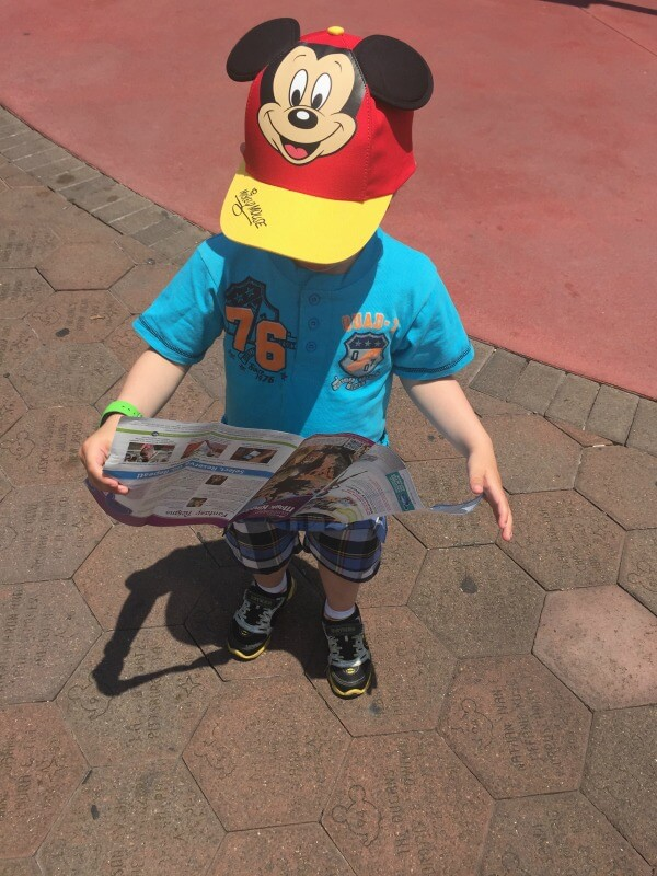 Toddler reading a map at Disney